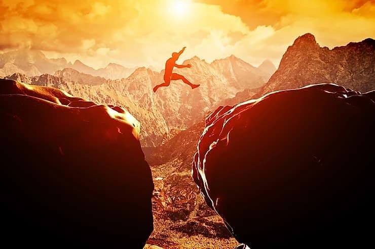 man jumping from a hill to another one
